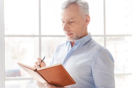 one senior man only: Making some business notes. Serious grey hair senior man in shirt writing something in his note pad and while standing in front of the window