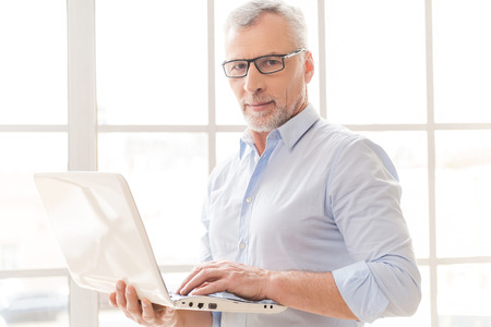 office attire: Supporting your business. Confident grey hair senior man in shirt working on laptop and looking at camera while standing in front of the window