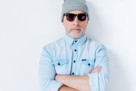 grey hair: Hipster is always hipster. Confident grey hair senior man in sunglasses and funky hat looking at camera and keeping arms crossed while standing against white background 스톡 사진