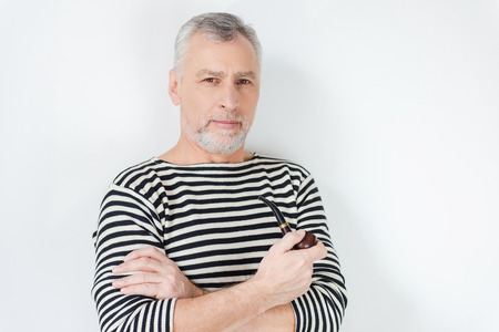 senior smoking: Confident sailor. Confident senior bearded man in striped clothing smoking a pipe and looking at camera while standing against white background Stock Photo