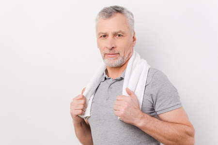 only one senior adult man: Relaxing after exercising. Confident grey hair senior man carrying towel on shoulders and looking at camera while standing against white background