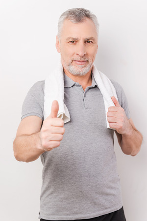 Keep your body fit. Confident grey hair senior man carrying towel on shoulders and showing his thumb up while standing against white background photo