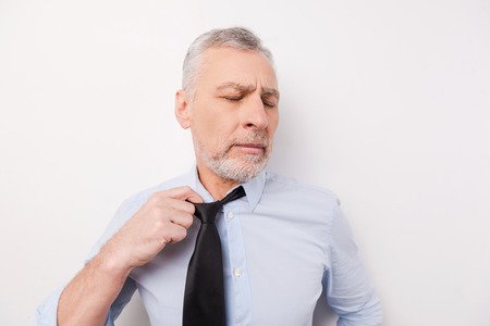 Feeling so tired. Tired senior man in shirt taking off his necktie while standing against white background photo
