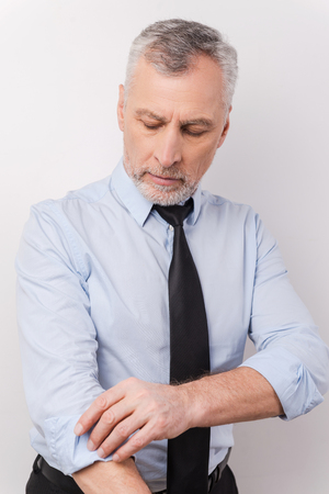 only men: Ready to work. Confident grey hair senior man in formalwear adjusting his sleeve while standing against white background