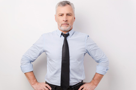 one senior man only: Confident and successful businessman. Confident grey hair senior man in shirt and tie holding hands on hip while standing against white background Stock Photo