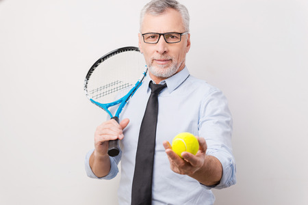 take a break: Take a break! Confident grey hair senior man in shirt and tie holding tennis racket and stretching out tennis ball while standing against white background