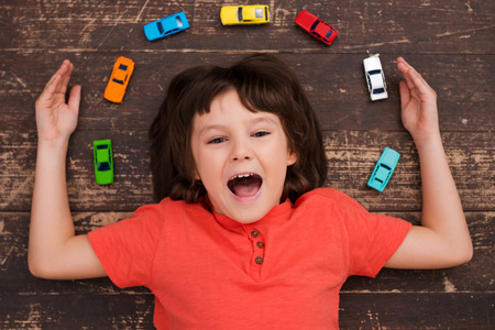 lying down on floor: More cars more joy! Top view of a little boy lying on the floor looking at camera and smiling Stock Photo