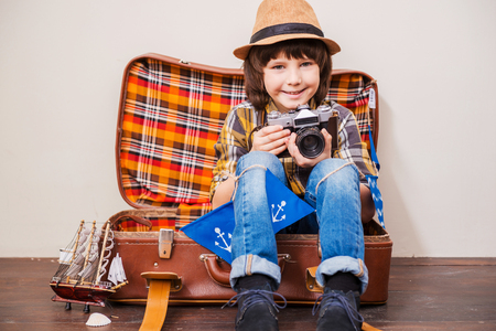 say cheese: Say cheese! Little boy in headwear holding camera and smiling while sitting in suitcase against brown background