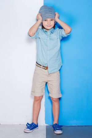 beautiful little boys: Life in colors. Full length of handsome little boy adjusting his hat and looking at camera while standing against colorful background
