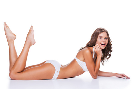 nude female body model: Feeling confident in her perfect body. Attractive young brown hair woman in white lingerie lying against white background and smiling