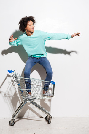Riding a shopping cart. Playful young African man riding in shopping cart against grey background Standard-Bild