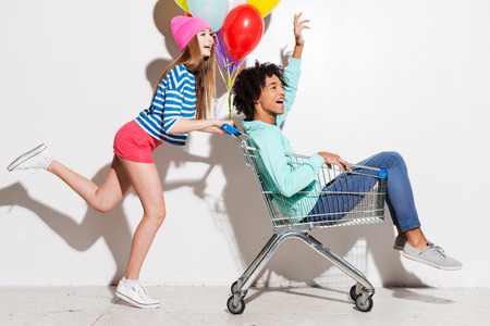 full shopping cart: Spending great time together. Happy young women carrying his boyfriend in shopping cart and smiling while running against grey background