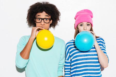 gestos de la cara: Amor burbuja doble. Pareja joven cobarde inflar globos mientras está de pie contra el fondo blanco