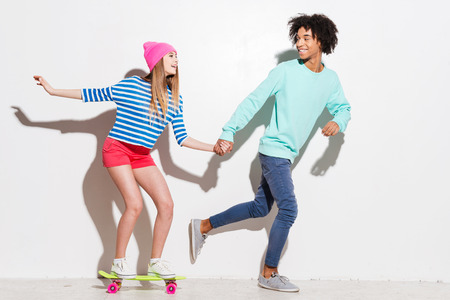 lifestyle caucasian: Spending great time together. Happy young women riding on skateboard while her boyfriend running near against white background