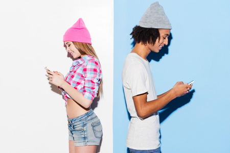 opposites: Opposites attract. Funky young couple holding mobile phones and standing back to back while standing against colorful background