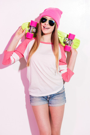 gestos de la cara: Muchacha del patinador feliz. Joven l�dica en sombreros de color rosa y gafas de sol celebraci�n patineta en sus hombros mientras est� de pie contra el fondo blanco
