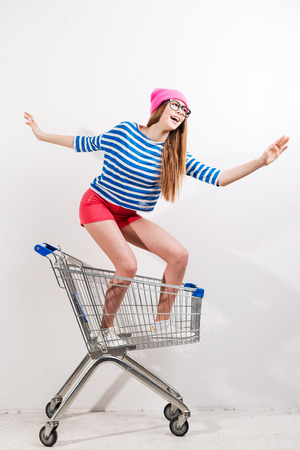 Extreme shopping. Playful young woman in headwear and glasses riding in shopping cart against grey background photo