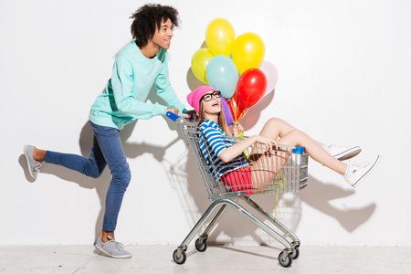 empujando: Pasar gran tiempo juntos. Hombre joven feliz que lleva a su novia hermosa en carro de compras y sonriendo mientras se ejecuta contra el fondo gris