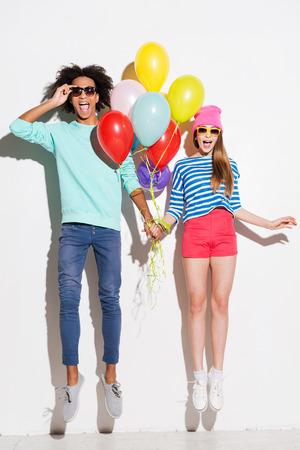 expresiones faciales: El amor en todos los colores del arco iris. Pareja joven cobarde con globos mientras saltando sobre fondo blanco