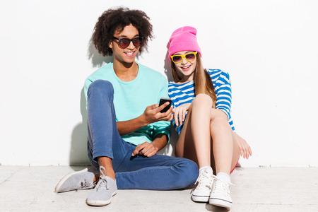 他の誰かに気付いていません。ファンキーな若いカップルの笑顔で白い背景に坐っている間携帯電話を見て