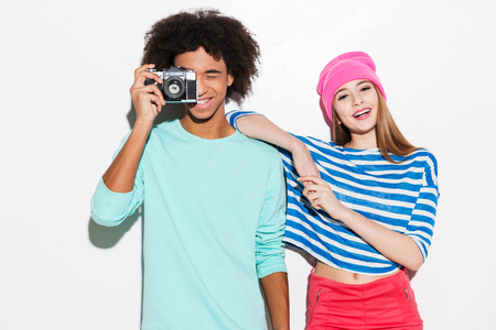 photography themes: Spending great time together. Funky young couple smiling while standing against white background Stock Photo