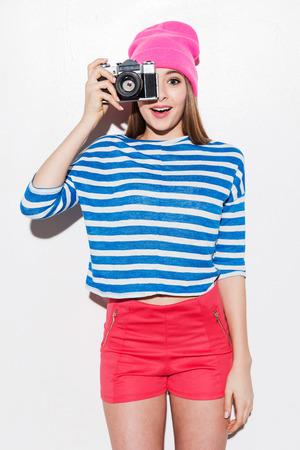 gestos de la cara: Tu Sonrie! Mujer joven juguetona en ropa funky mirando a trav�s de una c�mara mientras est� de pie contra el fondo blanco