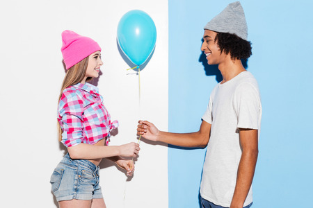 young add: Add some colors. Handsome young African man giving a blue balloon to his girlfriend while standing against colorful background