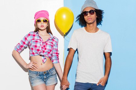 They are cool! Funky young couple holding yellow balloon and looking at camera while standing against colorful background