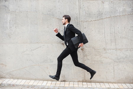 Hurrying to the new goals. Happy young man in formalwear holding briefcase while running in front of the concrete wall