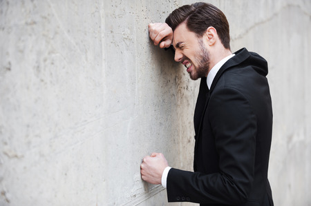 Depressed businessman. Side view of depressed young man in shirt and tie leaning at the wall and keeping eyes closed photo