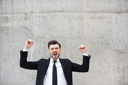 euphoria: Everyday winner. Happy young man in formalwear keeping arms raised and expressing positivity while standing against the concrete wall Stock Photo