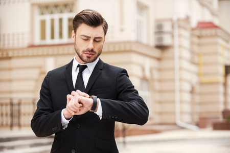 I will be in time. Handsome young man in formalwear looking at his watch while standing at the street