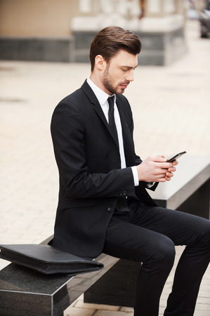 concentrates: Staying connected anytime and anywhere. Confident young man in formalwear holding mobile phone while sitting outdoors Stock Photo