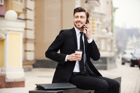 businessman smiling: A pleasant escape from the office. Confident young man in formalwear holding mobile phone and cup of coffee while sitting outdoors