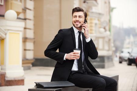 hombre tomando cafe: Un escape agradable de la oficina. Hombre joven confidente en ropa formal que sostiene el tel�fono m�vil y la taza de caf� mientras se sienta al aire libre