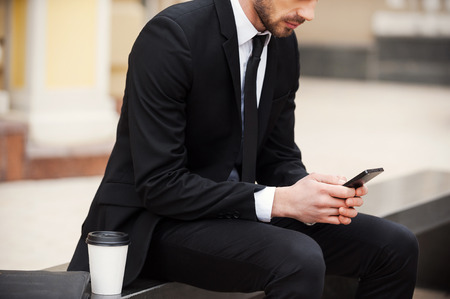 Staying connected anytime and anywhere. Cropped picture of young man in formalwear holding mobile phone while sitting outdoors