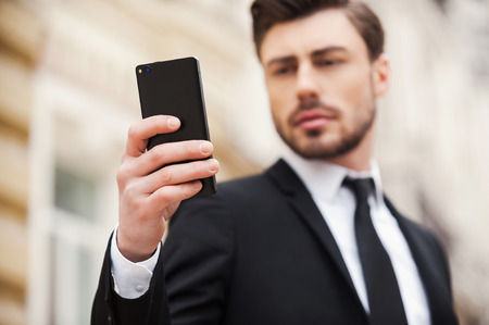 concentrates: Always connected. Confident young man in formalwear holding mobile phone while standing outdoors Stock Photo