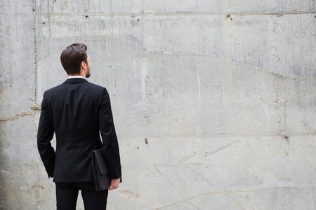 facing a wall: Facing a wall. Rear view of young man holding briefcase while standing outdoors and against the concrete wall
