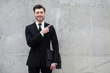 only man: Reliable expert. Handsome young man holding briefcase while standing outdoors and against the concrete wall Stock Photo