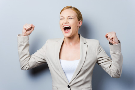 closed fist: What a lucky day! Happy young businesswoman keeping arms raised while standing against grey background