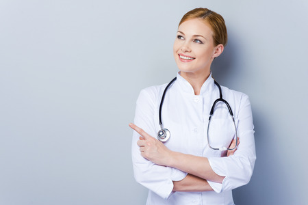Look over there! Confident female doctor in white uniform looking away and pointing while standing against grey background