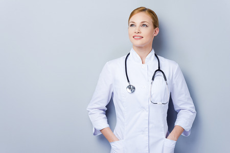 In searching of new professional solutions. Thoughtful female doctor in white uniform looking away and holding hands in pockets while standing against grey background