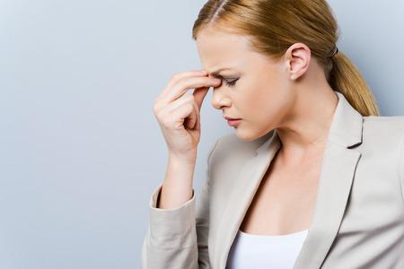 mujer trabajadora: El dolor de cabeza est� matando. Vista lateral de la deprimida joven empresaria tocar su cara y mantener los ojos cerrados mientras est� de pie contra el fondo gris
