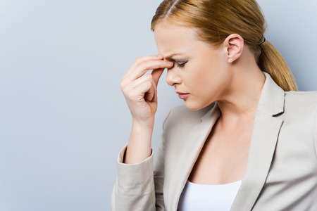 white collar worker: Headache is killing. Side view of depressed young businesswoman touching her face and keeping eyes closed while standing against grey background