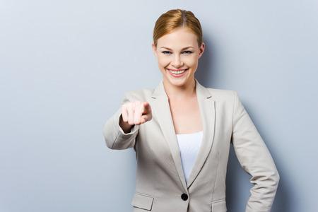 Ik kies jou! Mooie jonge zakenvrouw wijst je terwijl je tegen een grijze achtergrond Stockfoto