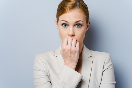 A little bit nervous. Nervous young businesswoman biting her nails while standing against grey background