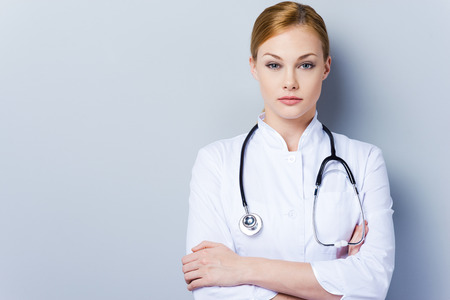 i am here: I am here to take care of you health. Confident female doctor in white uniform keeping arms crossed while standing against grey background