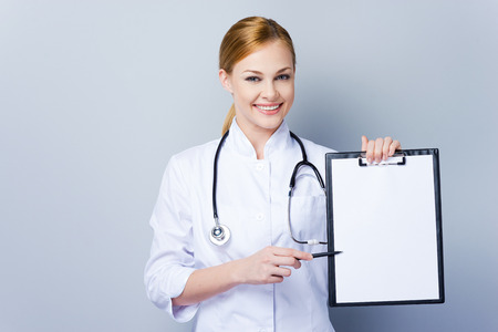 outstretching: Everything is ok, here you can read your diagnose. Confident female doctor in white uniform outstretching clipboard and looking at camera while standing against grey background Stock Photo