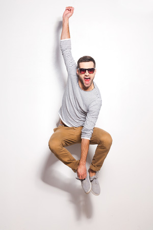 sex symbol: Just having fun. Excited young man jumping in front of the white wall and keeping mouth open Stock Photo