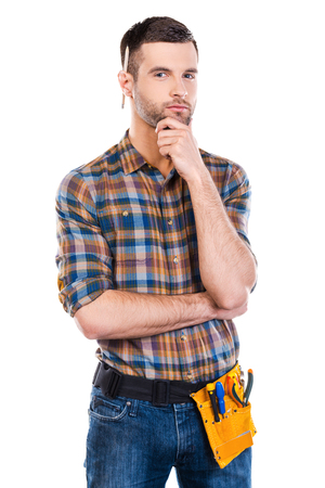 maintenance engineer: Thinking about your problem. Handsome young male carpenter with tool belt holding hand on chin and looking at camera while standing against white background